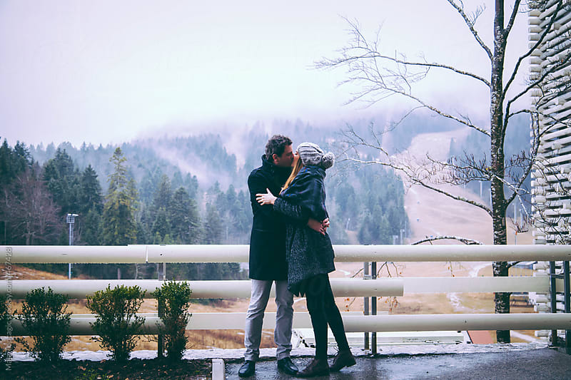 A couple kissing in the rain in the mountains by Maja Topcagic for Stocksy United