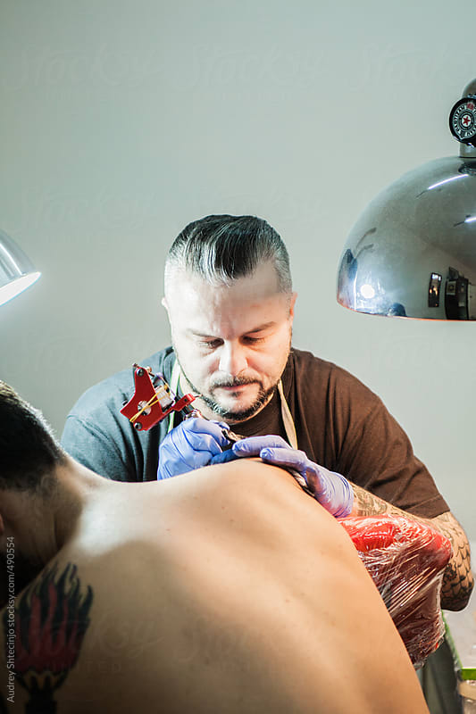 Rockabilly Tattoo artist tatooing by Audrey Shtecinjo for Stocksy United