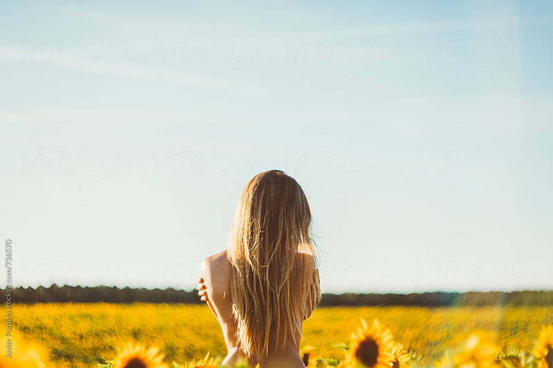 nude woman is looking at sunflowers  by Javier Pardina for Stocksy United