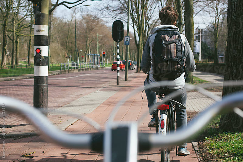 A man on his bicycle cycling thru the streets by Koen Meershoek for Stocksy United