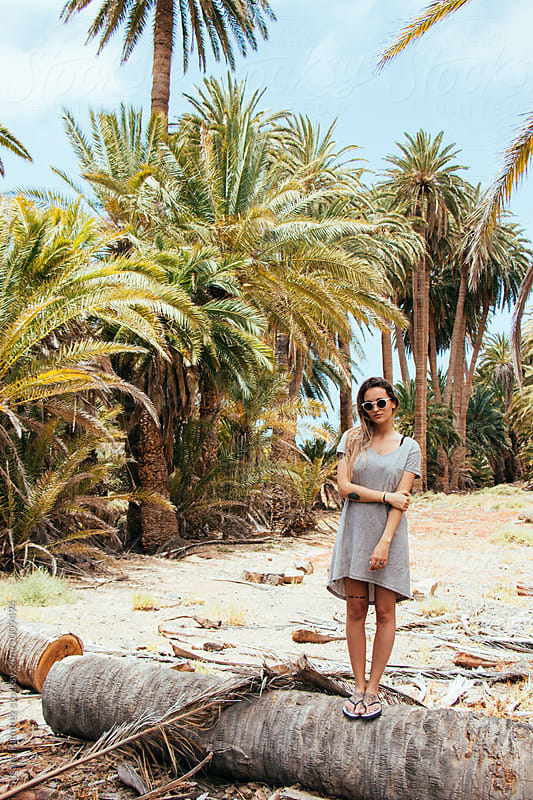 Fashion young woman between palm trees by Susana Ramírez for Stocksy United