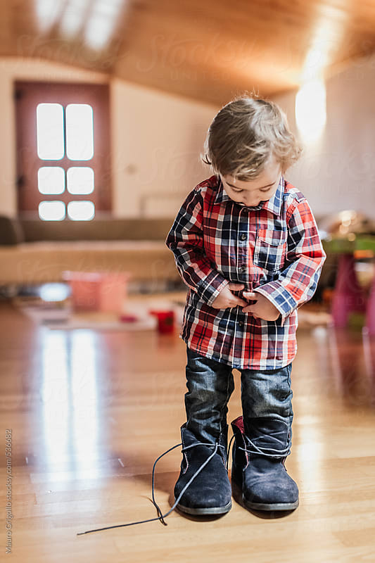 Little boy playing at home with big shoes by Mauro Grigollo for Stocksy United