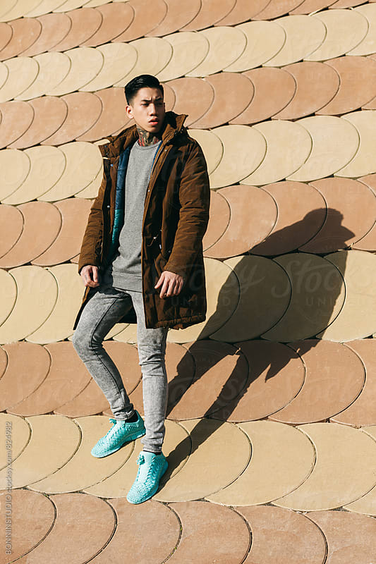 Portrait of an asian man standing in front of a wall on winter. by BONNINSTUDIO for Stocksy United