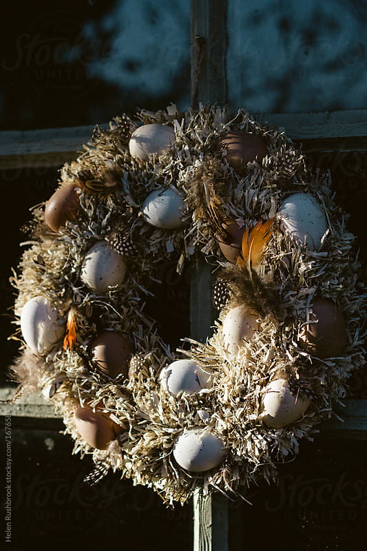 Easter Wreath hanging on a door by Helen Rushbrook for Stocksy United