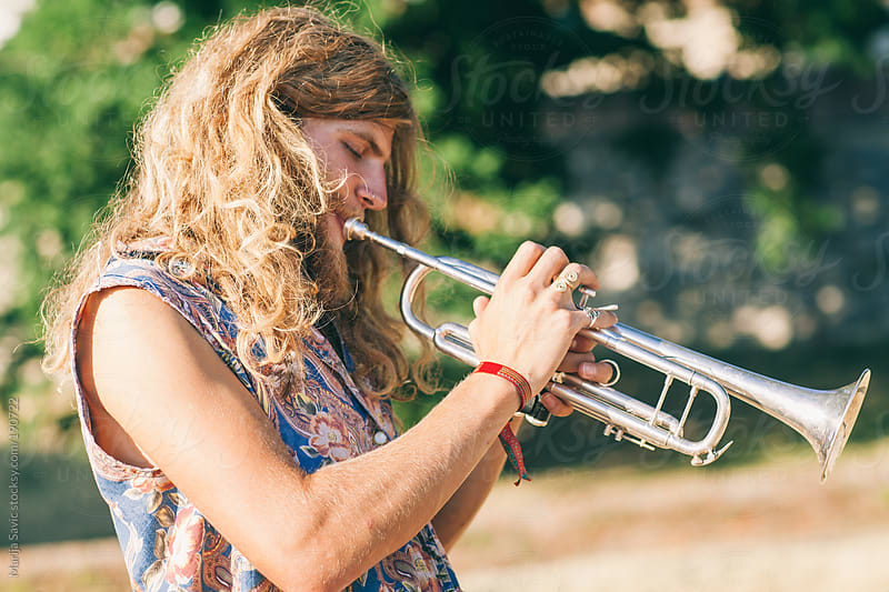 Young Hippie Playing Trumpet in Nature by Marija Savic for Stocksy United
