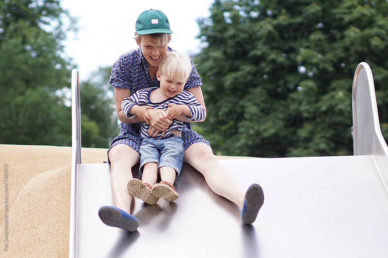 Mom and toddler son having fun in the slide at the playground by Per Swantesson for Stocksy United