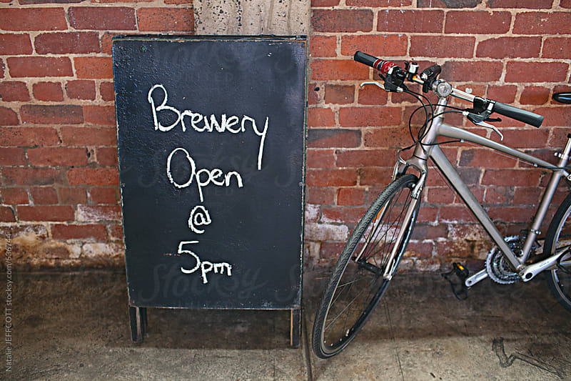 chalkboard sign at a micro brewery with bicycle by Natalie JEFFCOTT for Stocksy United