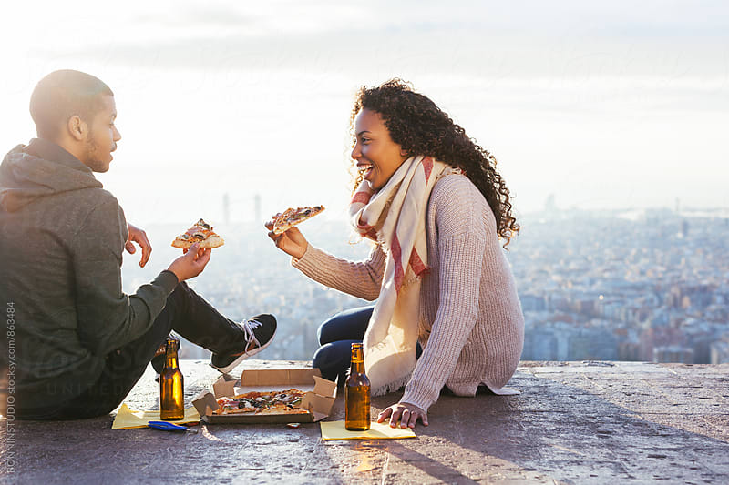 Young couple sitting eating pizza above Barcelona at sunset. by BONNINSTUDIO for Stocksy United