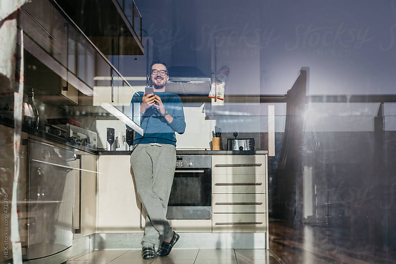 Man Send Text Message With a Mobile Phone in the Kitchen by HEX. for Stocksy United