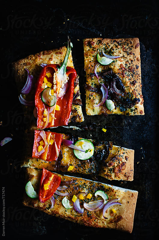 Roasted vegetables on flat bread. by Darren Muir for Stocksy United