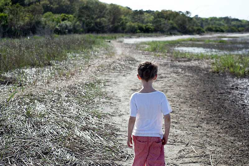 Boy walks along sandy beach with tall grass by Cara Slifka for Stocksy United