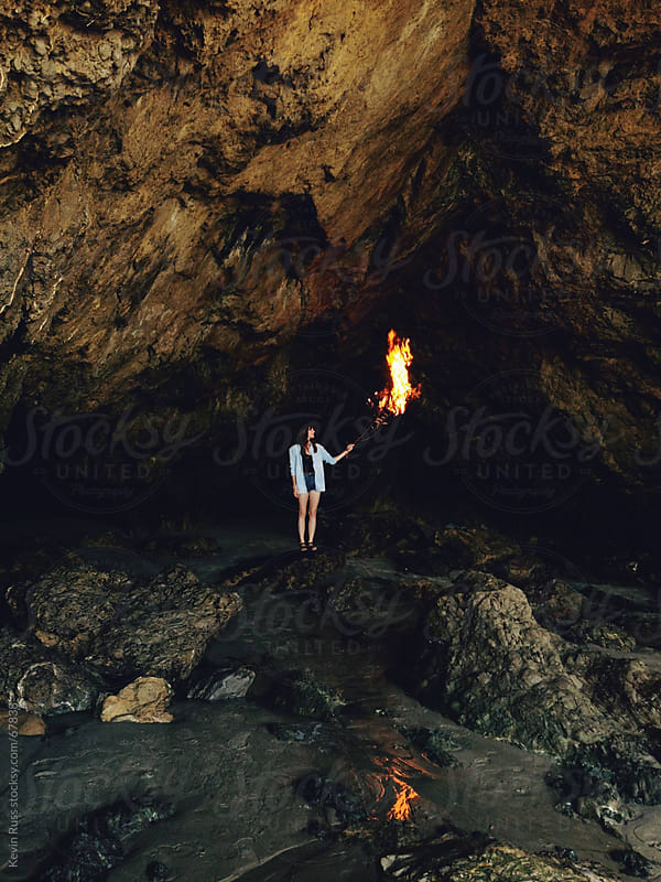 Woman Holding Burning Branch in Sea Cave by Kevin Russ for Stocksy United