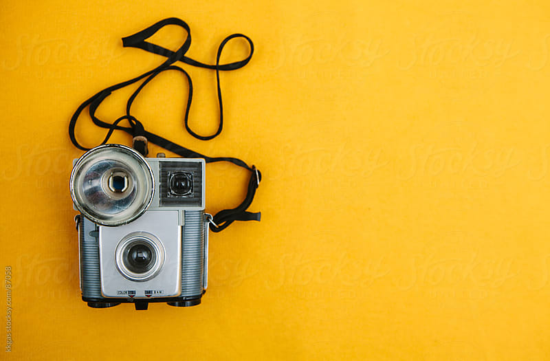Vintage camera on a yellow background. by kkgas for Stocksy United