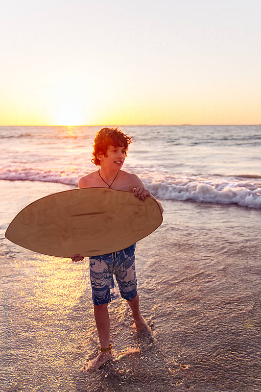 Boy with a skim board at the beach at sunset in summer by Angela Lumsden for Stocksy United