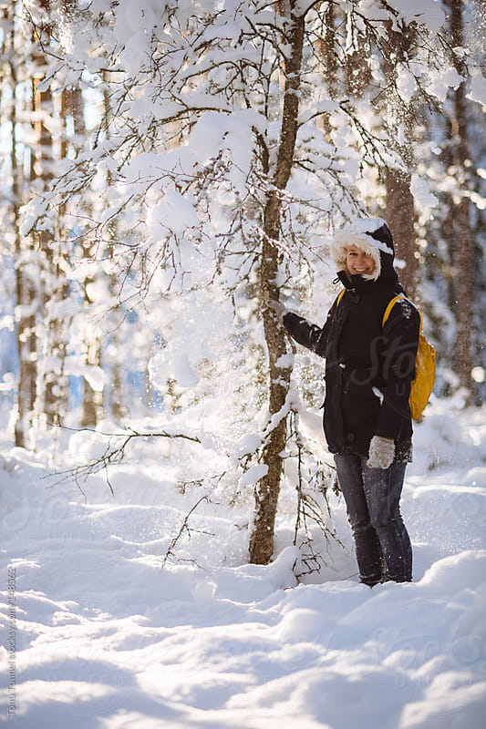 A scandinavian girl shaking a tree in a snowy forest by Tõnu Tunnel for Stocksy United