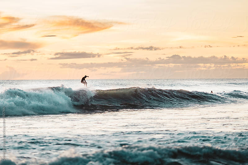A Surfer Riding a Wave in Nicaragua by Daniel Inskeep for Stocksy United