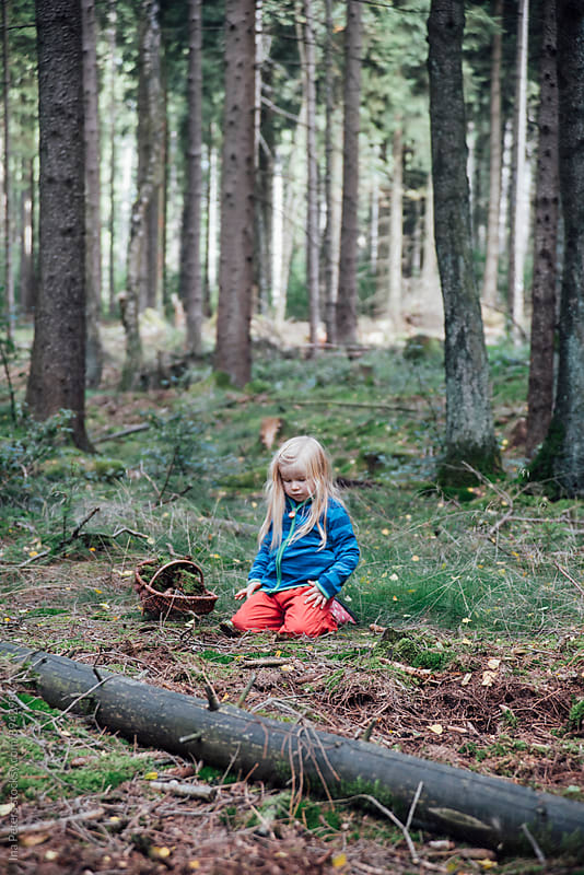 People: Girl collecting moss in the woods by Ina Peters for Stocksy United
