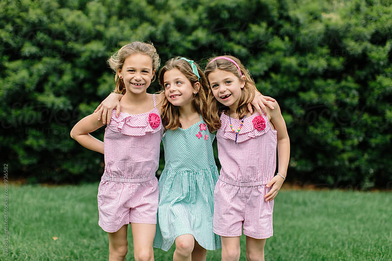 Three cute young sisters with their arms around each other by Jakob for Stocksy United