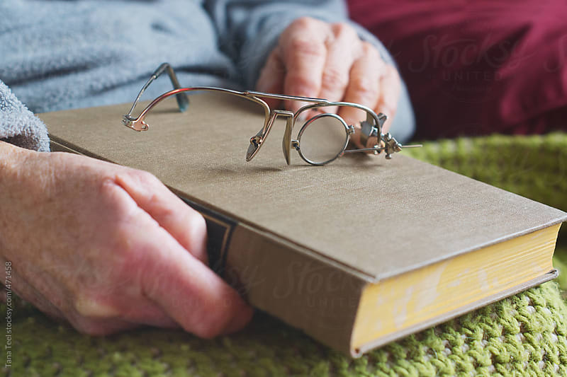 Homemade reading glasses placed on a book held by older woman by Tana Teel for Stocksy United