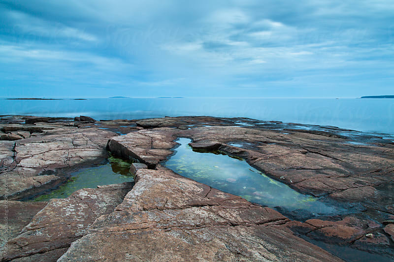 Tide pool reflecting blue sky on rocks near ocean by Matthew Spaulding for Stocksy United