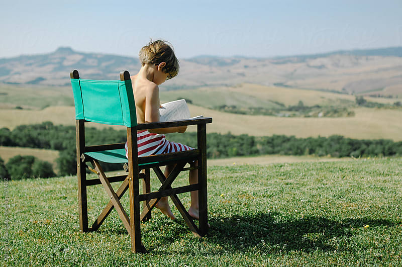 Boy reading a book with a view of Tuscany by Kirstin Mckee for Stocksy United