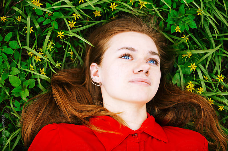 Top view of a young woman lying down in grass day dreaming. by Ilya for Stocksy United
