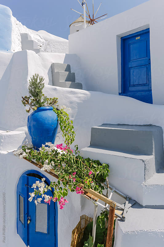 Back street in Santorini, Greece, with steps, blue door and window by Paul Phillips for Stocksy United