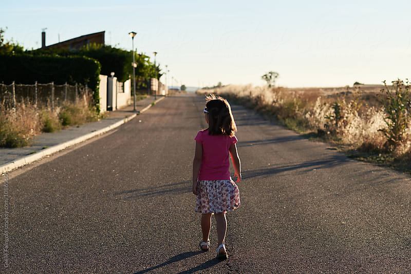 Rear view of little kid in skirt walking along road in countryside by Guille Faingold for Stocksy United