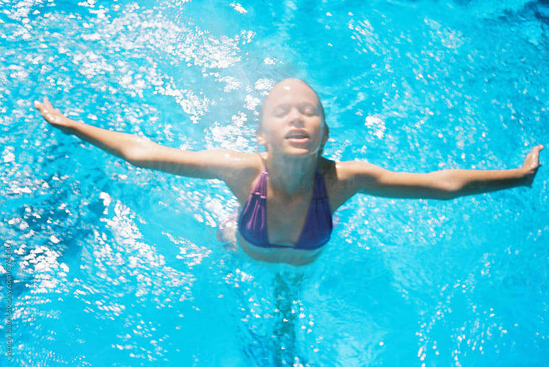 girl jumping for joy in blue sunshine pool by wendy laurel for Stocksy United