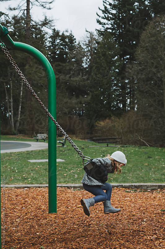 Preschool girl having fun on swing in winter by Rob and Julia Campbell for Stocksy United