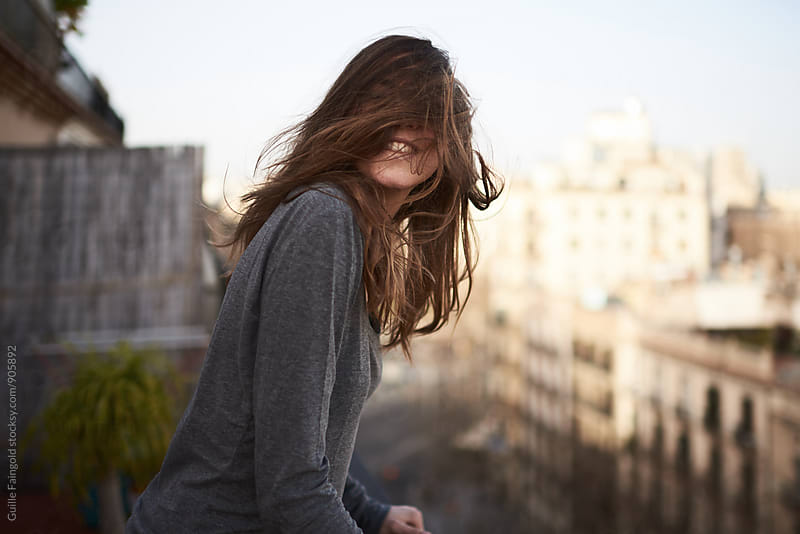 Cheerful woman with windy hair covering her face by Guille Faingold for Stocksy United