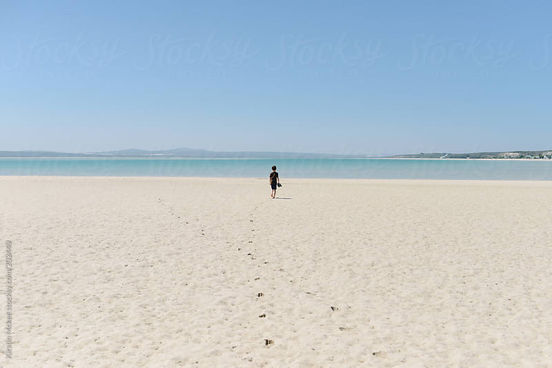 Boy walking along a deserted beach by Kirstin Mckee for Stocksy United