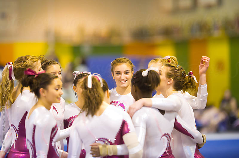Gymnasts Huddle During Competition by Brian McEntire for Stocksy United