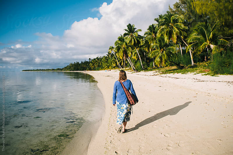 Woman walking along a beach on the western side of Aitutaki Island, Cook Islands. by Thomas Pickard for Stocksy United