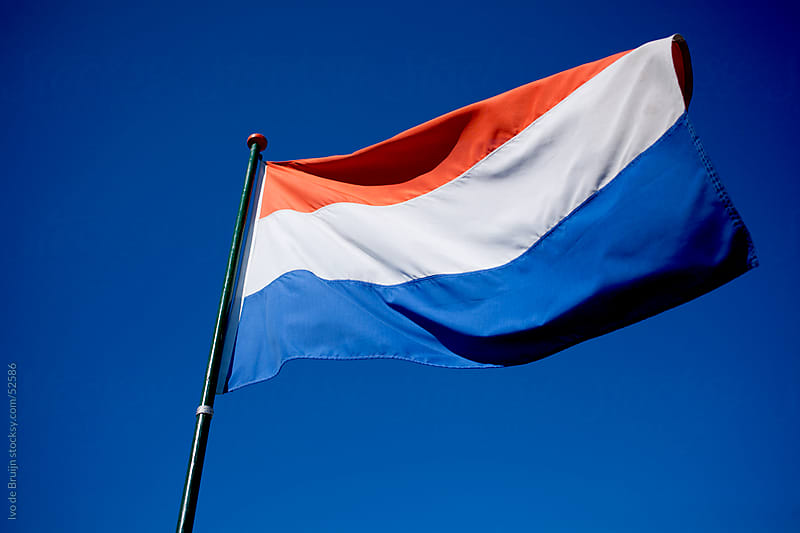 A waving dutch flag in a clear blue sky by Ivo de Bruijn for Stocksy United