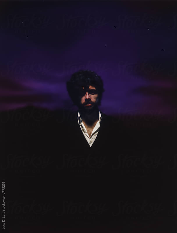 Dark Polaroid portrait of a young bearded man against a surreal nocturnal sky. by Luca Di Lotti for Stocksy United