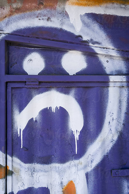 Sad face painted on a iron door. by Mauro Grigollo for Stocksy United