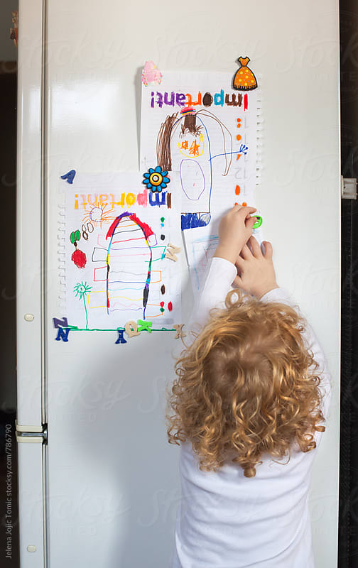 Child drawings on a fridge by Jelena Jojic Tomic for Stocksy United