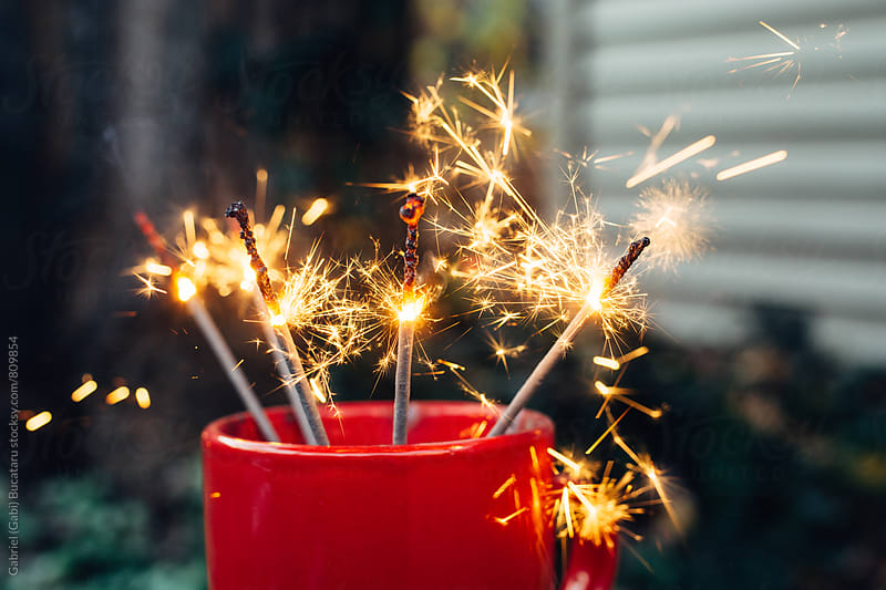 Red festive cup with lit sparklers by Gabriel (Gabi) Bucataru for Stocksy United