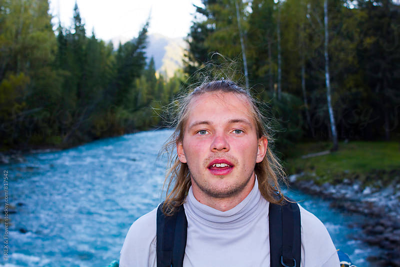 Portrait of young man looking at camera while standing against of mountain river by Danil Nevsky for Stocksy United