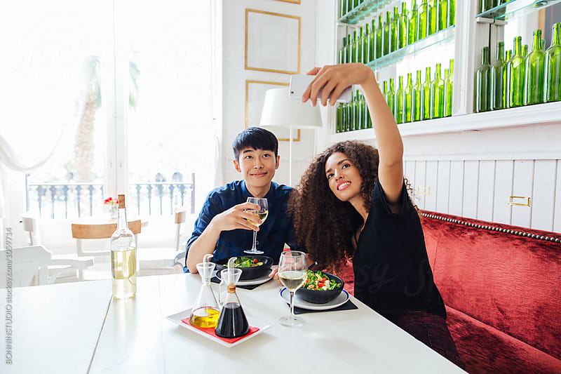 Multi-ethnic couple taking a selfie whilst eating in a cool restaurant.  by BONNINSTUDIO for Stocksy United