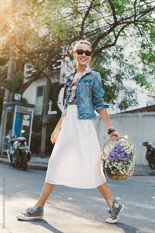 Girl walking and carrying a wooden basket full of flowers. by Jovo Jovanovic for Stocksy United