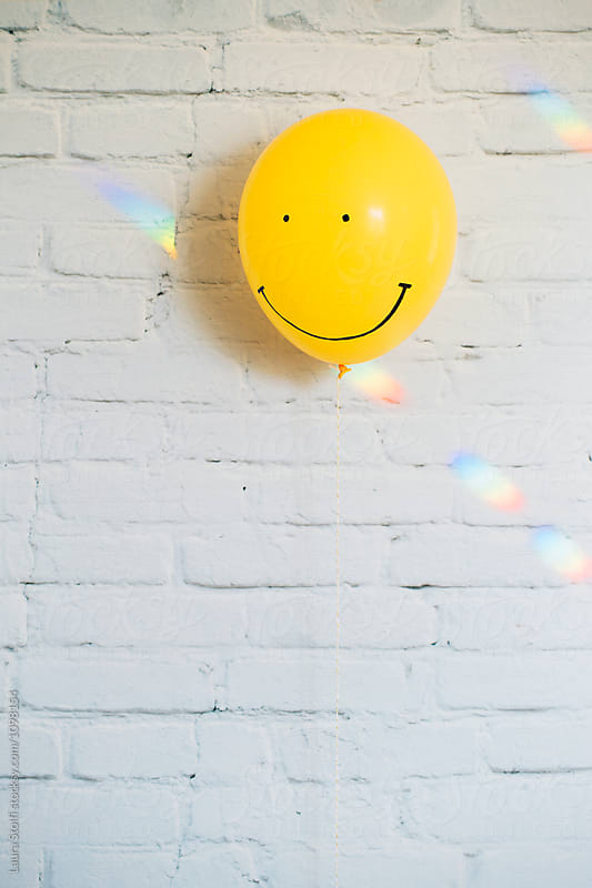 Smiling face painted on yellow balloon and rainbow lights by Laura Stolfi for Stocksy United