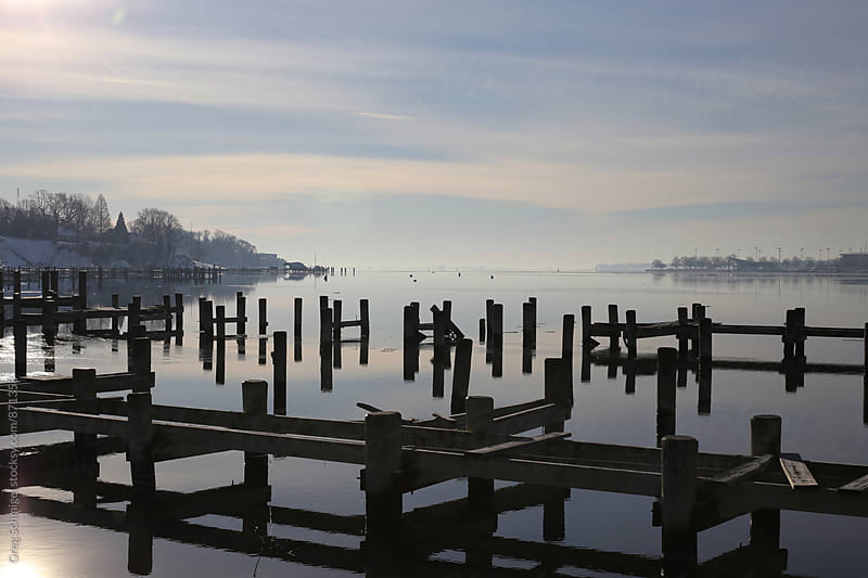 Early morning winter view of pilings in a river with snowy banks and fog by Greg Schmigel for Stocksy United