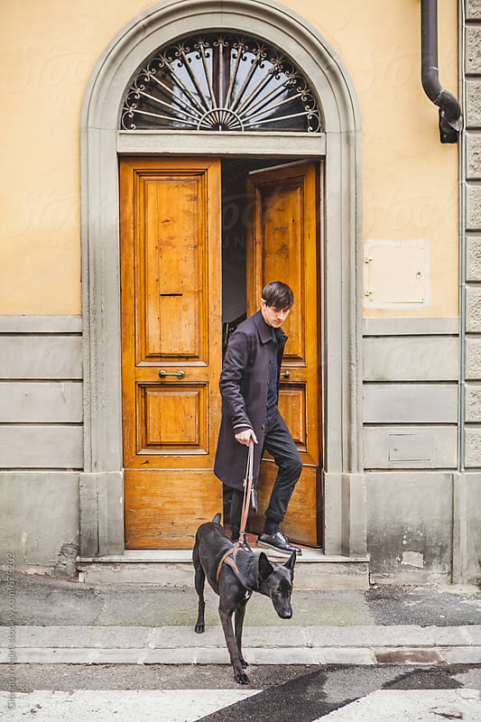 Young Man Going Out with his Black Dog by Giorgio Magini for Stocksy United