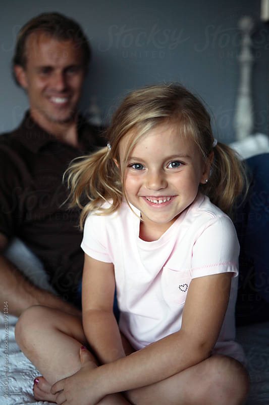 Daughter WIth Ponytails Smiling With Dad in Background by Dina Giangregorio for Stocksy United