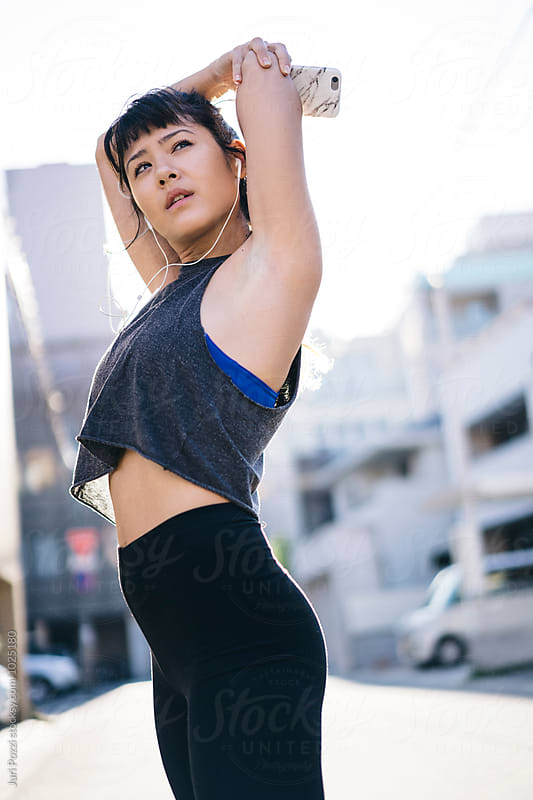 Fit Asian woman stretching before running by Juri Pozzi for Stocksy United