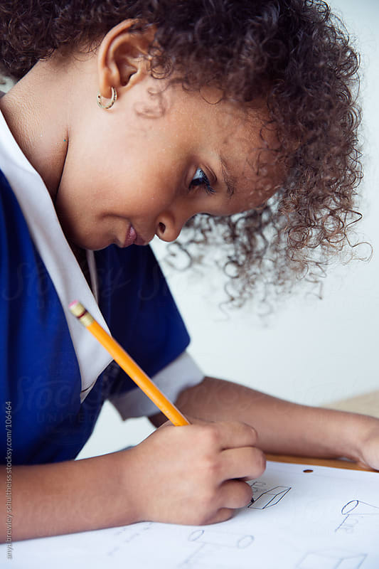 Young girl with curly hair doing homework by anya brewley schultheiss for Stocksy United