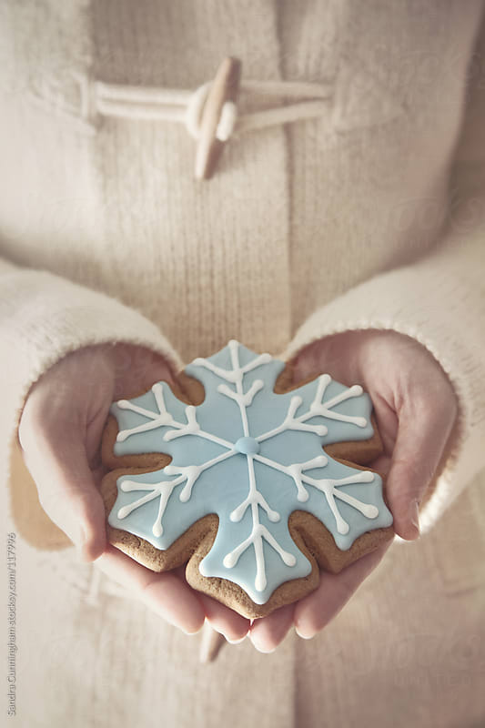 Woman holding a snowflake cookie by Sandra Cunningham for Stocksy United