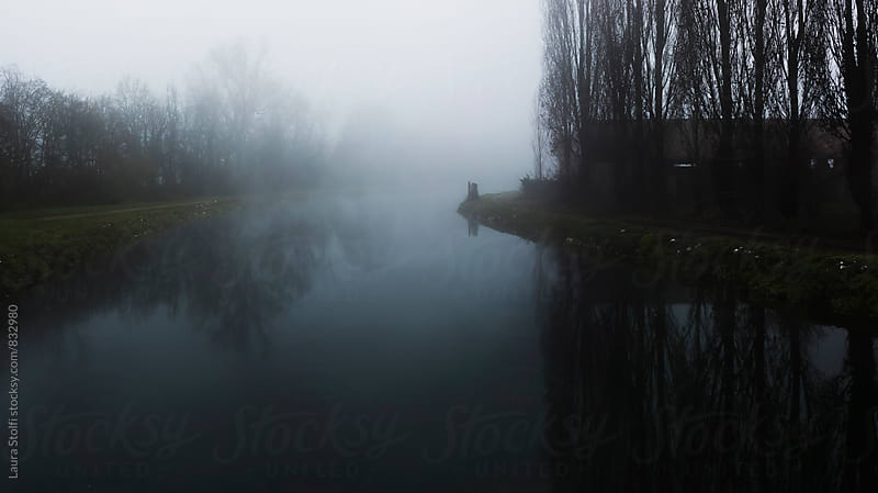 Mystic river: leafless trees and abandoned farm reflection in river's water by Laura Stolfi for Stocksy United